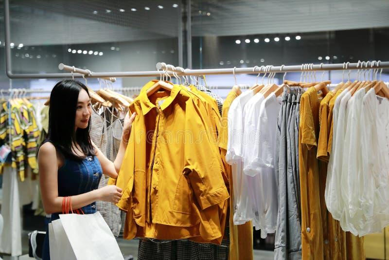 Het gelukkige de vrouwenmeisje van Azië Chinese Oostelijke oosterse jonge in winkelen in wandelgalerij met zakken kiest kleren ui royalty-vrije stock foto's