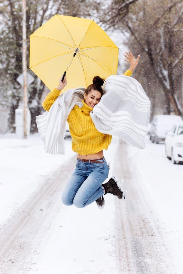 Het gelukkige donker-haired meisje gekleed in een gele sweater, jeans en een witte sjaal springt met een gele paraplu in sneeuw royalty-vrije stock afbeeldingen