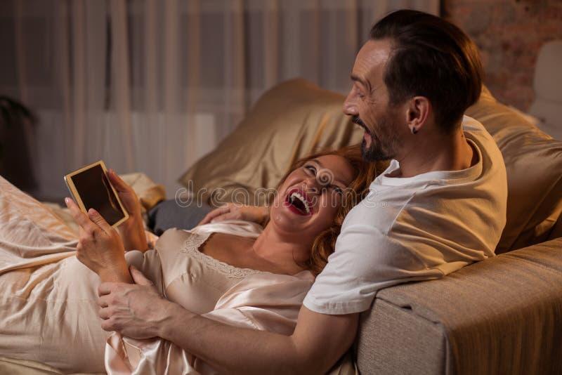 Het gelukkige echtgenoot en vrouwen onderhouden met gadget thuis stock afbeeldingen