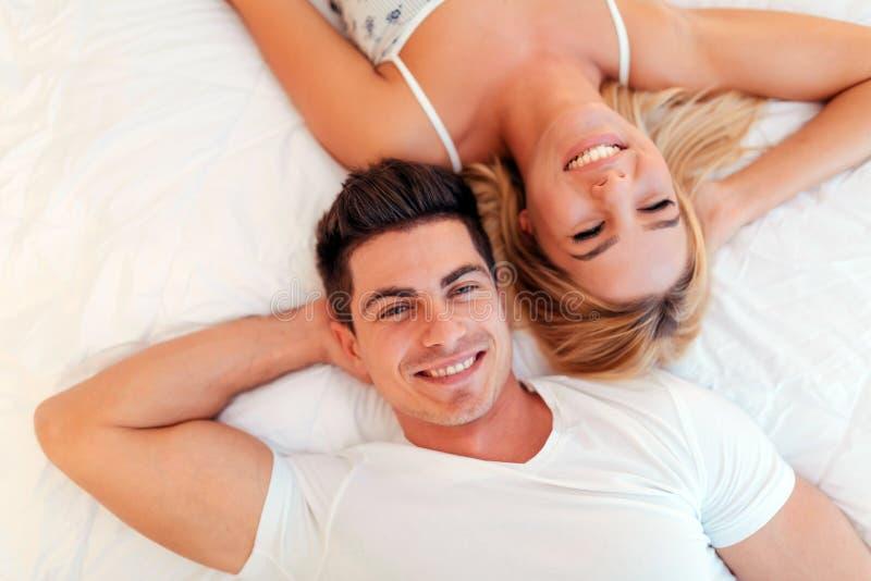 Het gelukkige echtpaar ontspannen die op bed liggen stock afbeelding