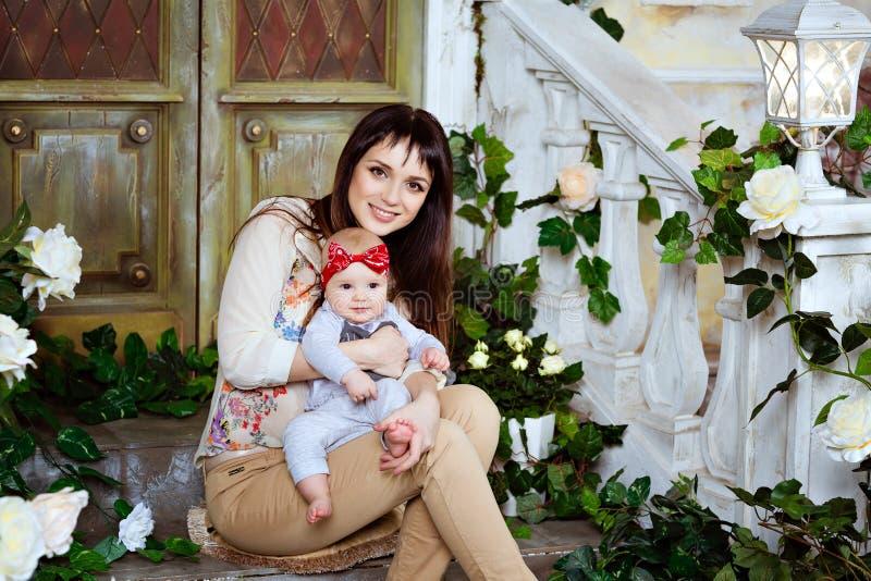 Het gelukkige en mooie mammabrunette houdt zijn aanbiddelijke baby DA royalty-vrije stock foto