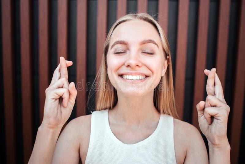 Het gelukkige en positieve blondemeisje bevindt zich en houdt haar ogen gesloten Zij glimlacht De jonge vrouw kruist haar stock foto's