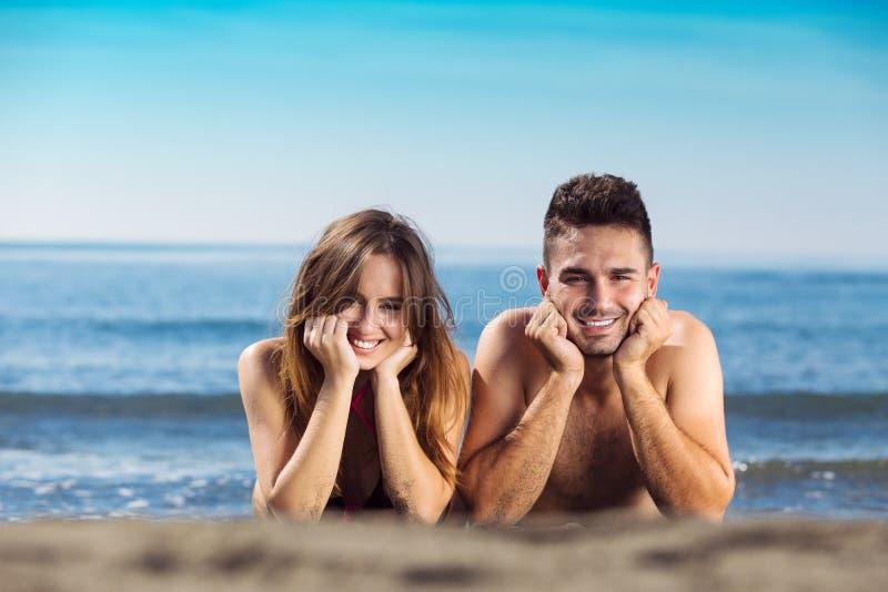 Het gelukkige enkel echtpaar legt op het strand stock afbeeldingen