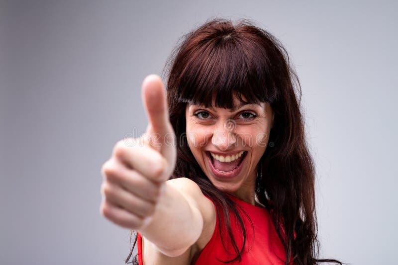 Het gelukkige enthousiaste vrouw geven duimen omhoog stock fotografie
