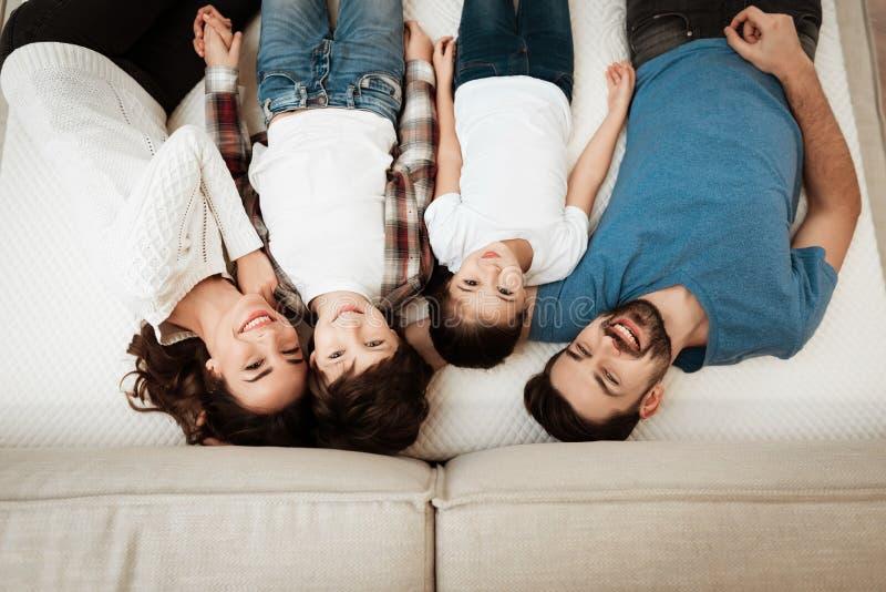 Het gelukkige familie genieten van van comfort ligt op matras binnen meubilairopslag royalty-vrije stock afbeelding