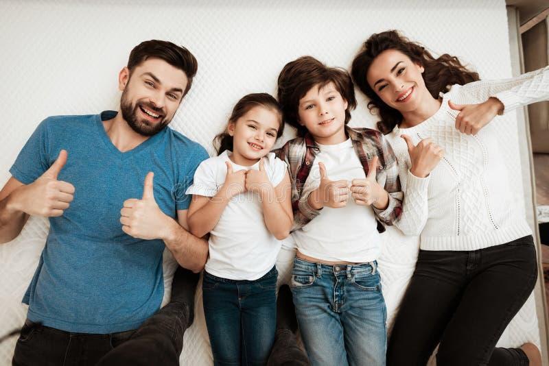 Het gelukkige familie genieten van van comfort ligt op matras binnen meubilairopslag stock afbeeldingen