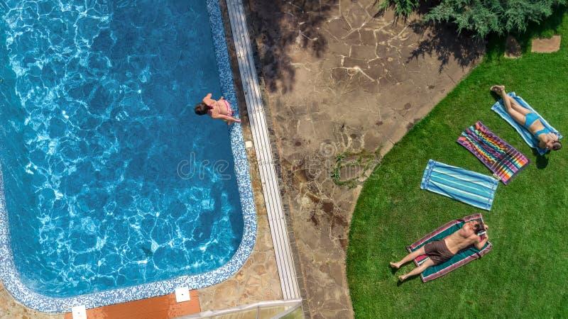 Het gelukkige familie ontspannen door zwembad, de luchthommelmening van hierboven van ouders en de jonge geitjes hebben pret op v stock fotografie