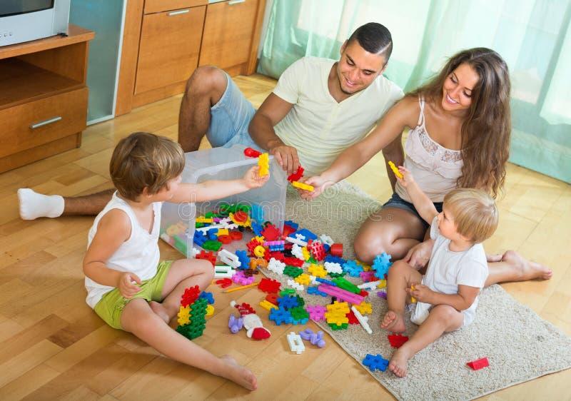 Het gelukkige familie spelen in huisbinnenland stock fotografie