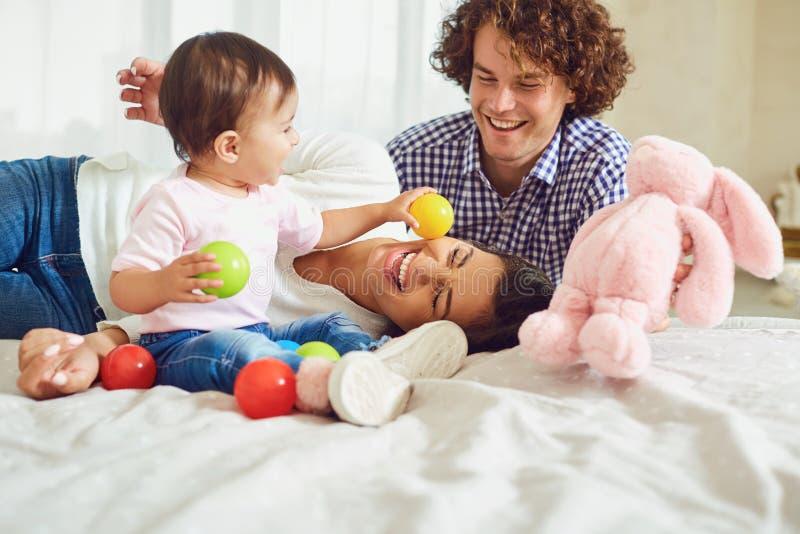 Het gelukkige familie spelen met de baby in de ruimte Jonge moeder en stock afbeelding