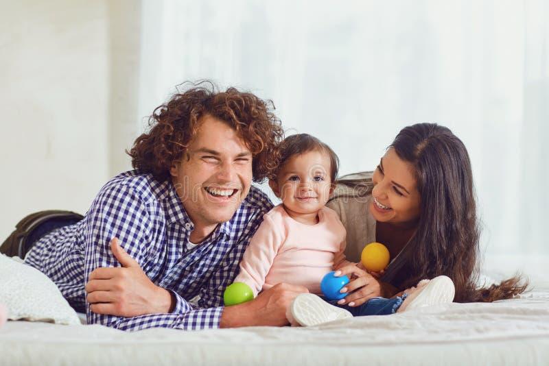 Het gelukkige familie spelen met de baby in de ruimte Jonge moeder en royalty-vrije stock fotografie