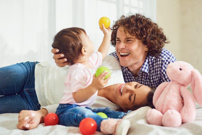 Het gelukkige familie spelen met de baby in de ruimte Jonge moeder en stock afbeeldingen