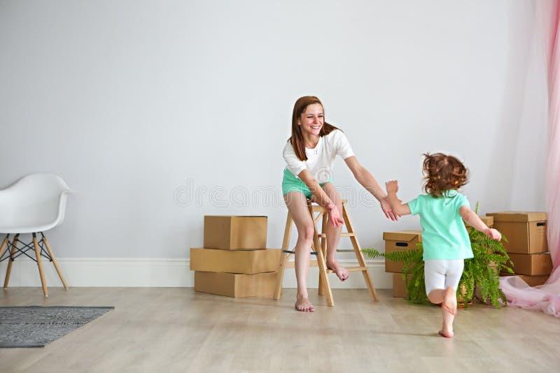 Het gelukkige familie spelen in nieuw huis Moeder en dochter die F hebben stock foto