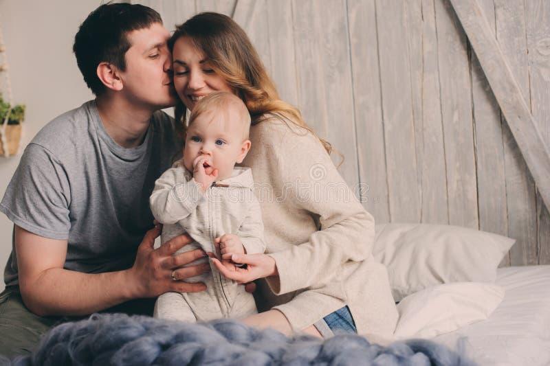 Het gelukkige familie spelen thuis op het bed Levensstijlvangst van moeder, vader en baby stock fotografie