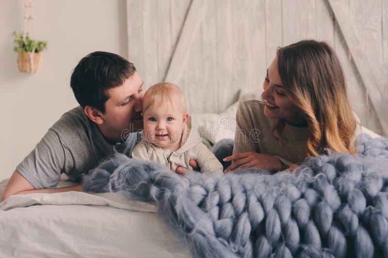 Het gelukkige familie spelen thuis op het bed Levensstijlvangst van moeder, vader en baby stock afbeeldingen