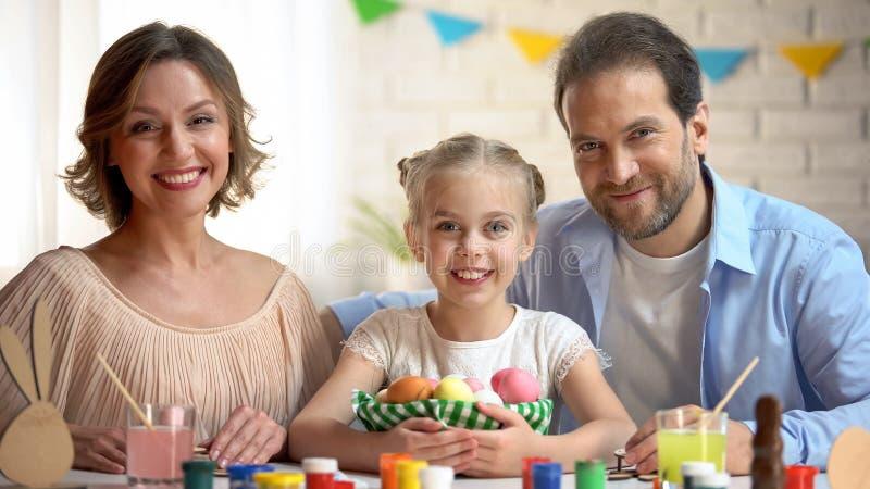 Het gelukkige familie stellen bij camera met Pasen-mand, oude traditie, viering stock fotografie