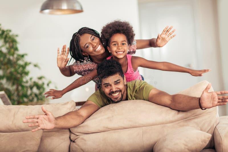 Het gelukkige familie stellen op de laag samen thuis stock foto