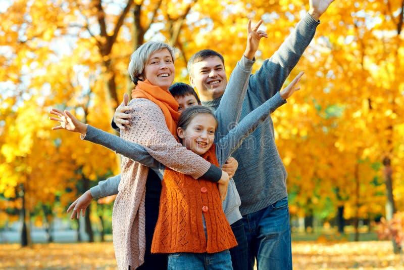 Het gelukkige familie stellen van, het spelen van en het hebben van pret in het park van de de herfststad Kinderen en ouders die  stock foto's