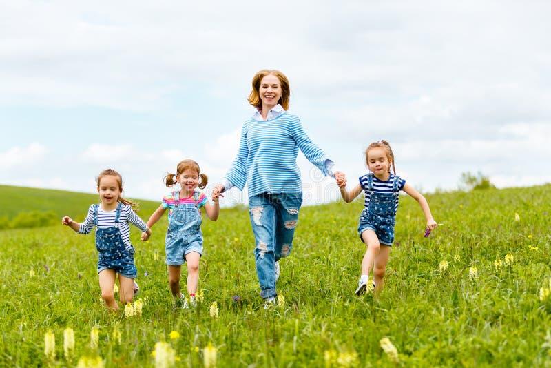 Het gelukkige familiemoeder en van de kinderendochter meisjes lachen en looppas royalty-vrije stock afbeelding