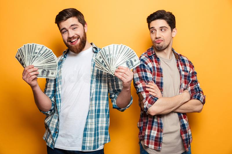 Het gelukkige gebaarde geld van de mensenholding en het bekijken de camera royalty-vrije stock afbeelding