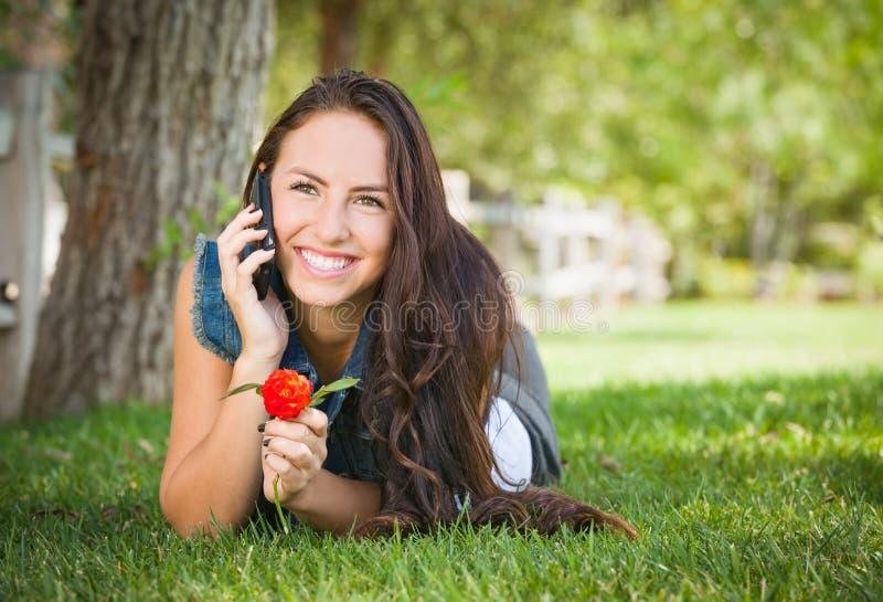 Het gelukkige Gemengde Wijfje die van de Rastiener op Celtelefoon spreken op Gazon stock foto