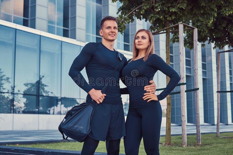 Het gelukkige geschiktheidspaar in een sportkleding, een sexy blondemeisje en een knappe spierkerel bevindt zich in de moderne st stock foto's