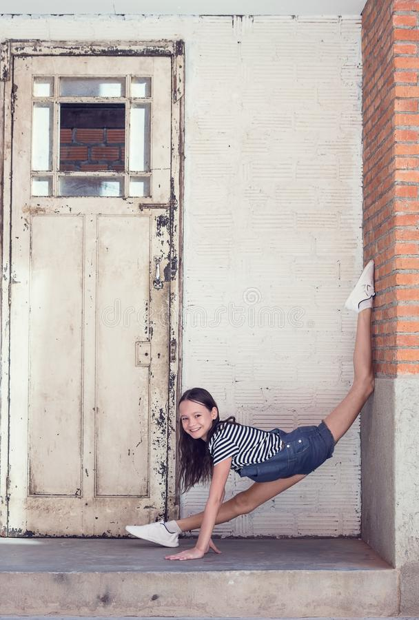 Het gelukkige glimlachen preteen girl do gymnastics in de deuropening naast oude houten deur in baksteen en concrete muur Openluc royalty-vrije stock afbeelding