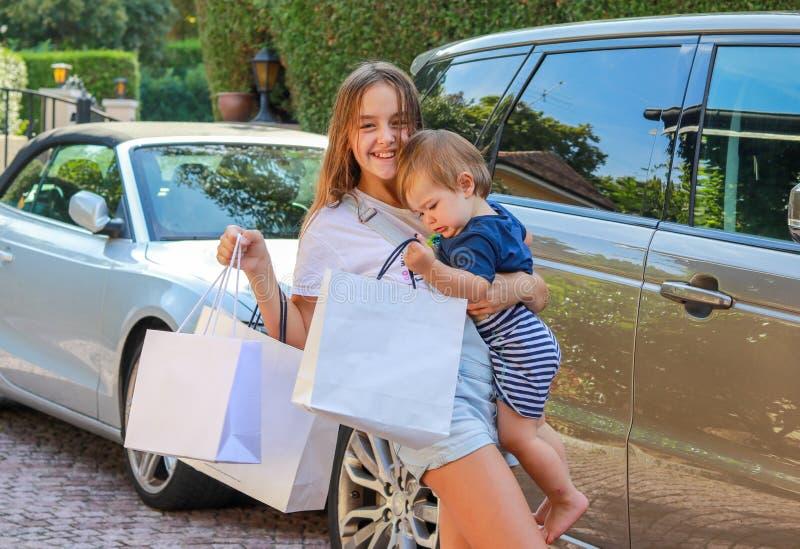 Het gelukkige glimlachen preteen meisje die met het winkelen zakken haar houden weinig broer die na het winkelen door auto terugk stock afbeeldingen