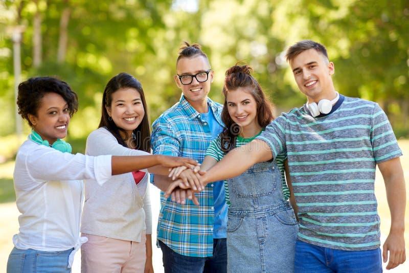 Het gelukkige het glimlachen vrienden stapelen dient park in stock fotografie