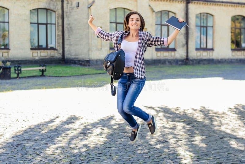 Het gelukkige glimlachen wekte het jonge vrouwelijke student springen, het vieren op royalty-vrije stock afbeelding