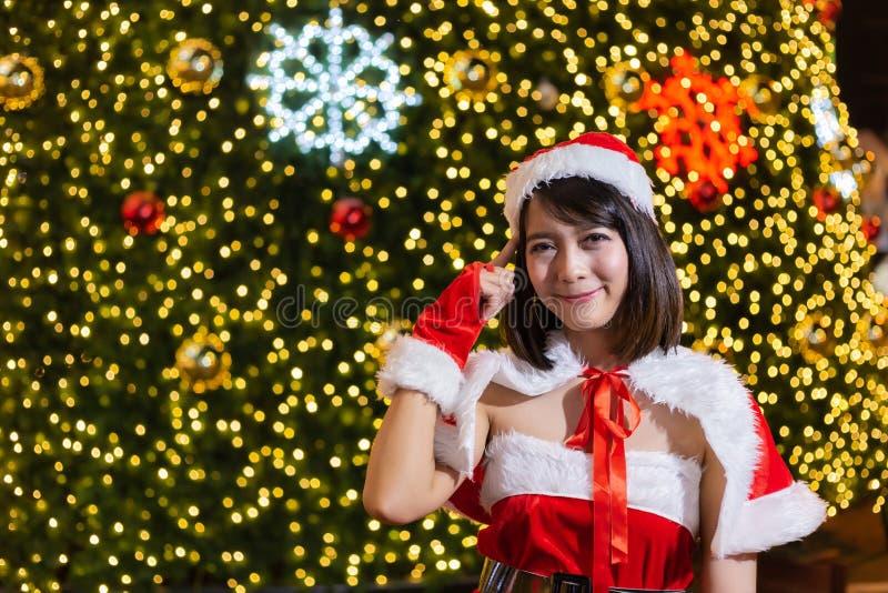 Het gelukkige glimlachende Kerstmanmeisje is leuk in rood kostuum met van de achtergrond Kerstmisboom viering in Kerstmis royalty-vrije stock afbeeldingen