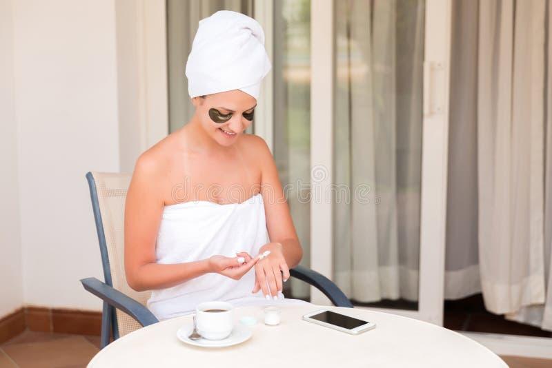 Het gelukkige glimlachende meisje vroeg in de ochtend op het terras van het hotel om haar handen met een bevochtigende huid te sm royalty-vrije stock foto's