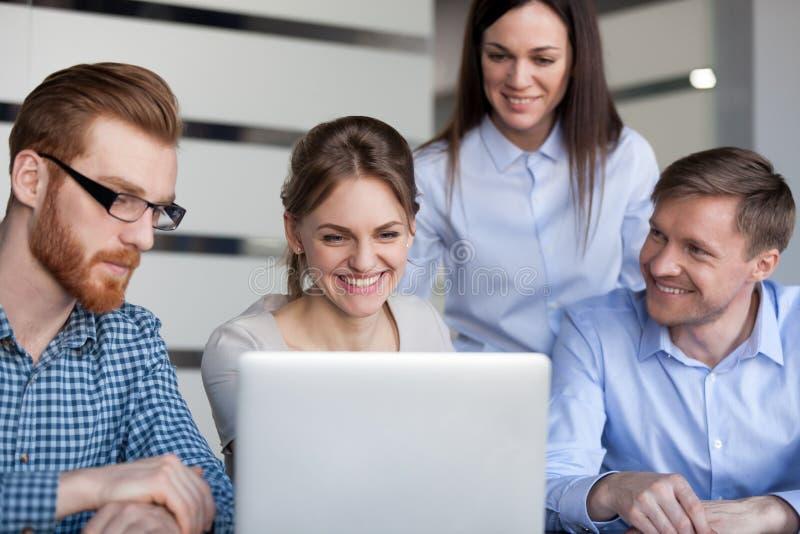 Het gelukkige glimlachende team die van bureauwerknemers pret hebben die laptop bekijken stock afbeeldingen