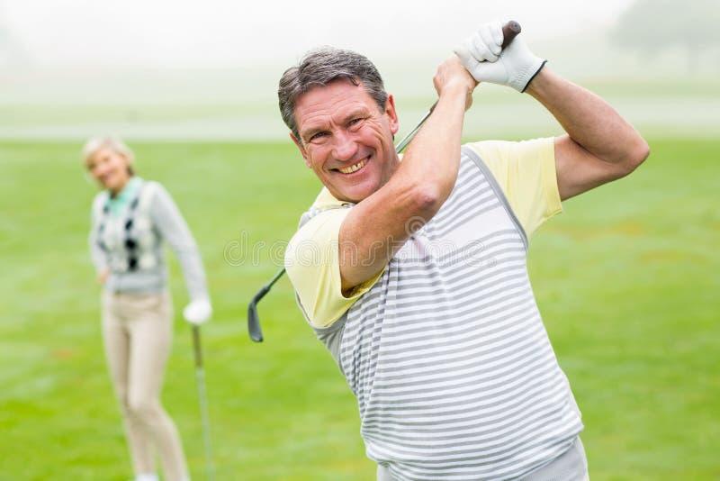 Het gelukkige golfspeler teeing weg met partner achter hem royalty-vrije stock foto