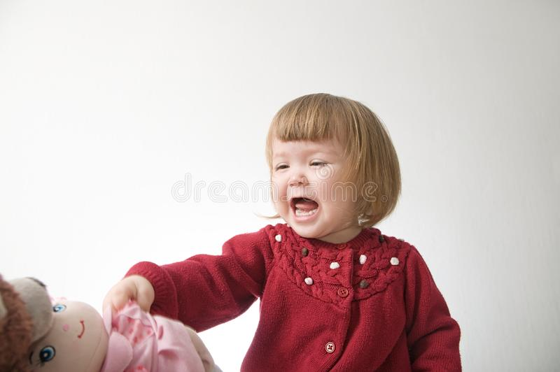 Het gelukkige grappige meisje emotionele spelen leuk Kaukasisch blond babymeisje met beer en pop royalty-vrije stock foto's