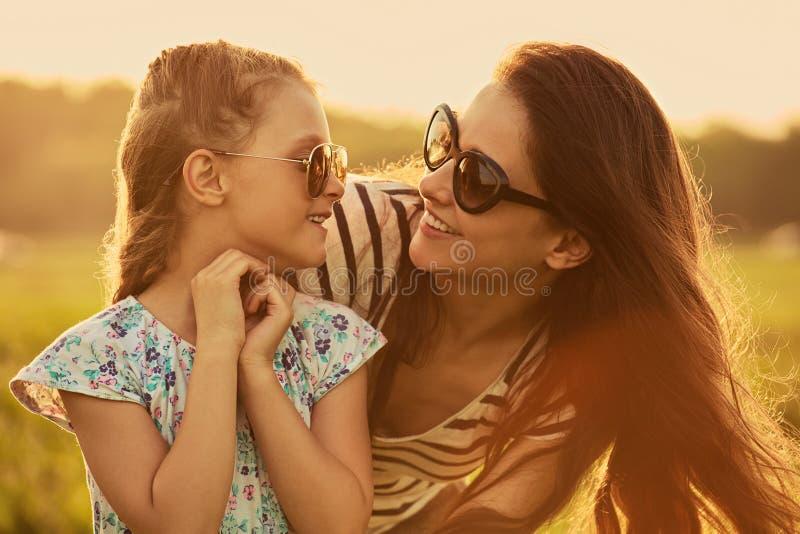 Het gelukkige haar moeder in in zonnebril omhelzen en meisje die van het manierjonge geitje elkaar met liefde op aardachtergrond  royalty-vrije stock foto