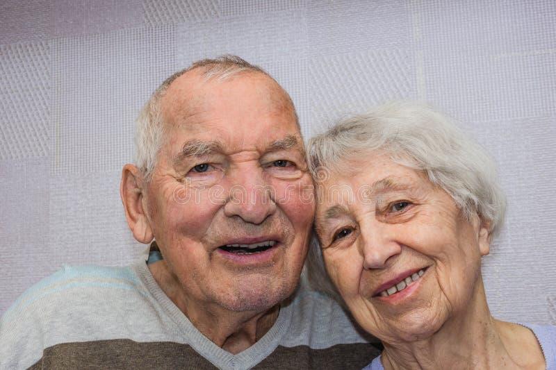 Het gelukkige hartelijke rijpe oude man en vrouwen omhelzen stock afbeeldingen