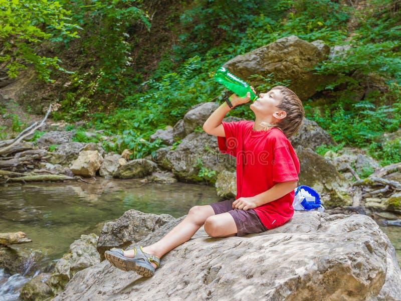 Het gelukkige het glimlachen drinkwater van de kindjongen op bosrivierrug stock foto