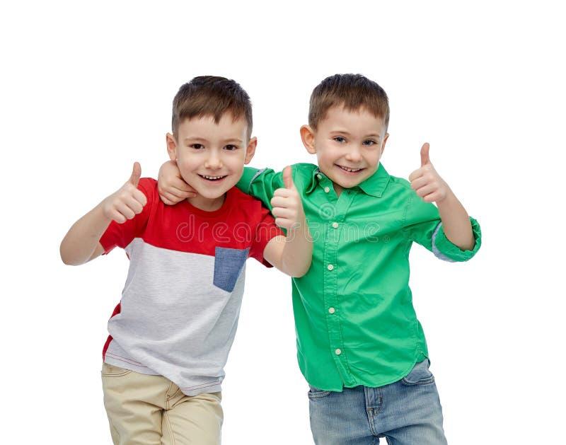 Het gelukkige het glimlachen kleine jongens tonen beduimelt omhoog stock afbeelding