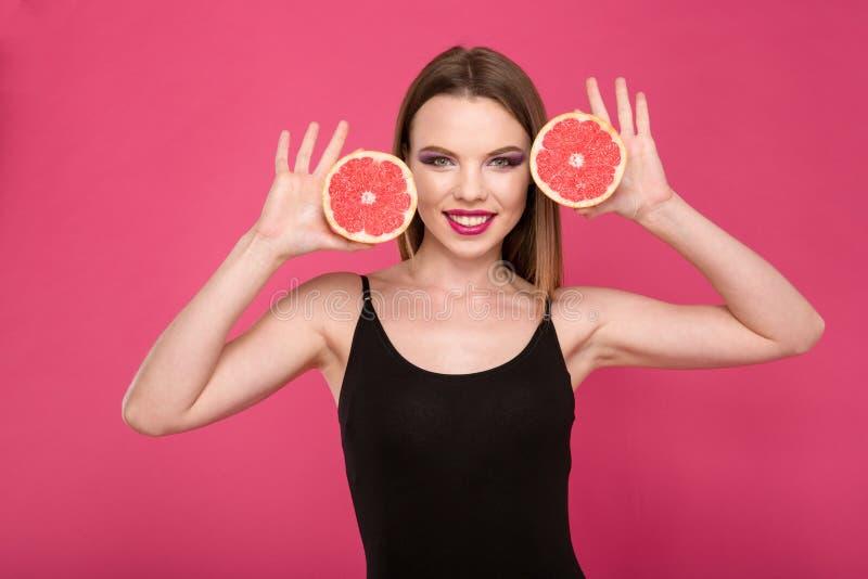 Het gelukkige het glimlachen meisje stellen met de twee helften van grapefruit royalty-vrije stock fotografie