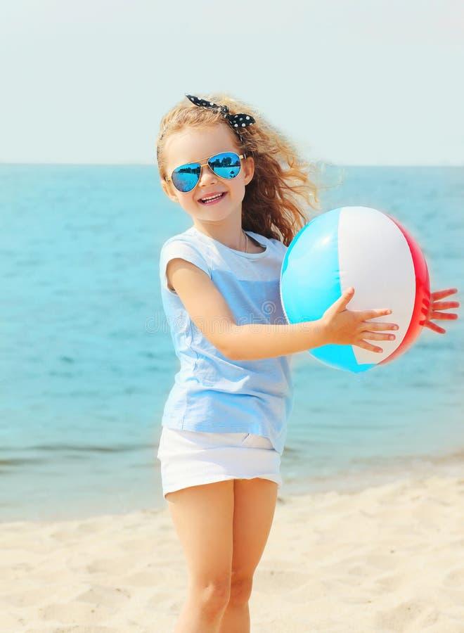 Het gelukkige het glimlachen meisjekind spelen met opblaasbare waterbal op strand dichtbij overzees royalty-vrije stock afbeelding