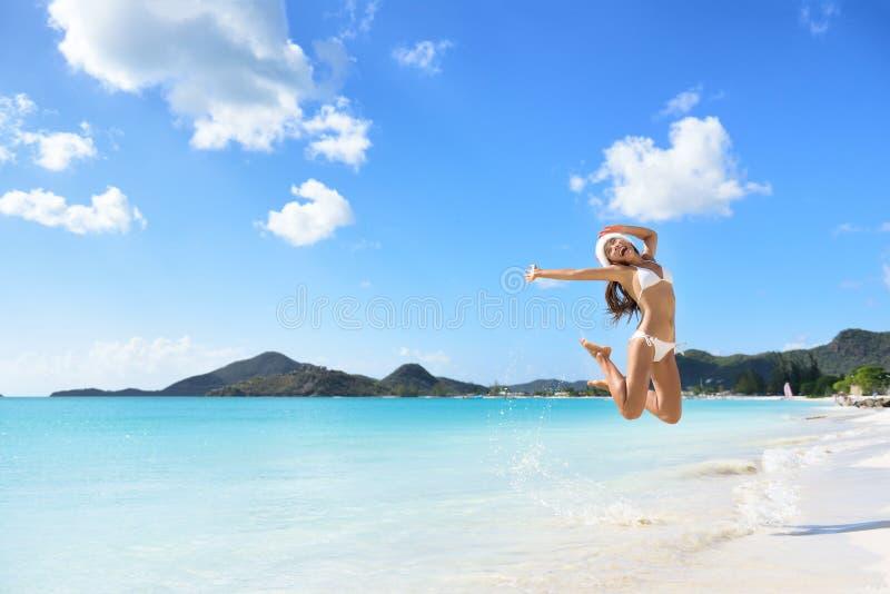 Het gelukkige het meisje van de Kerstmishoed springen van vreugde op strand stock foto's