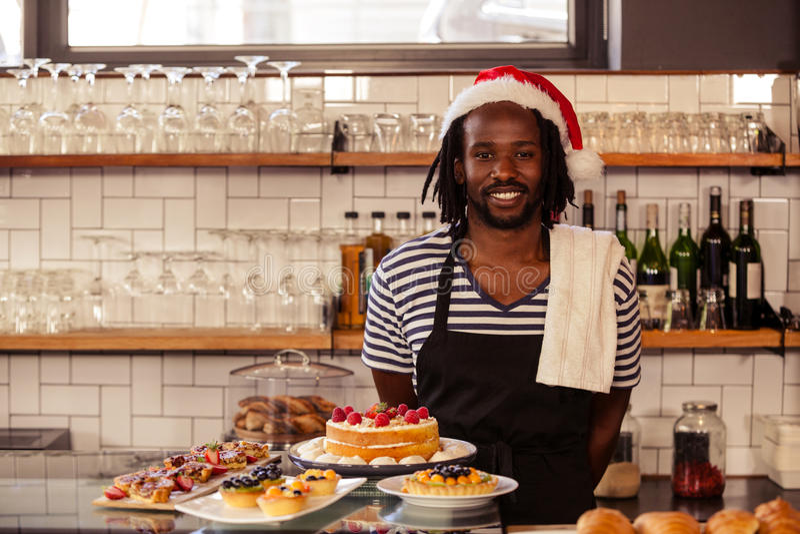 Het gelukkige hipsterarbeider stellen met Kerstmishoed stock foto