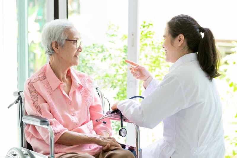 Het gelukkige hogere Aziatische vrouw en artsen of verpleegster spreken, vrouwelijke verzorger of vriendschaps ondersteunende gli stock afbeeldingen