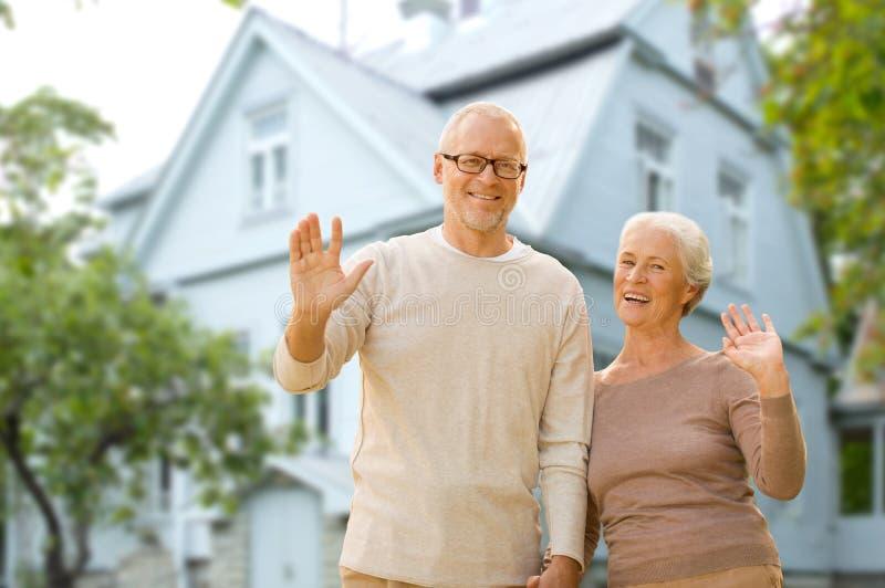 Het gelukkige hogere paar die overhandigt het leven huis golven stock foto's