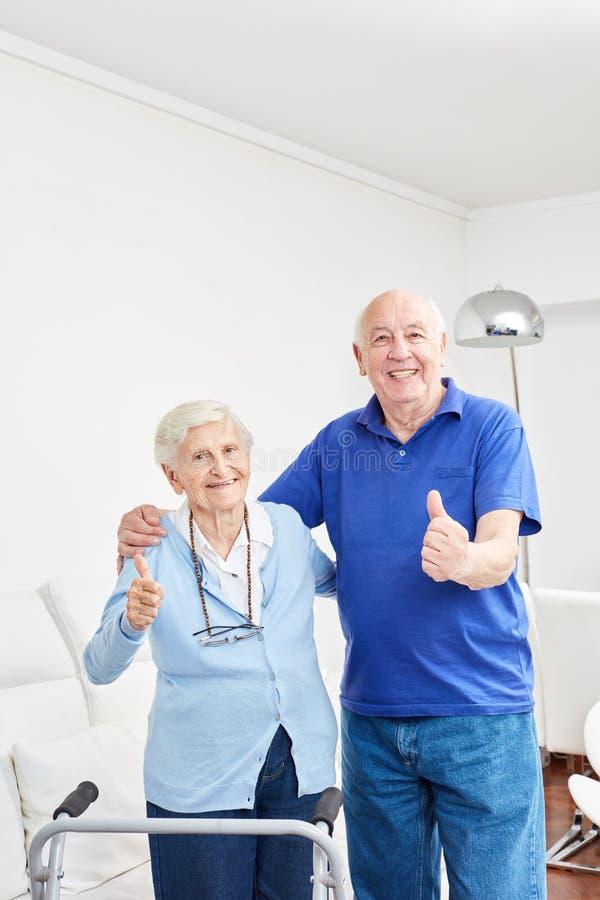 Het gelukkige hogere paar houdt omhoog hun duimen stock foto's