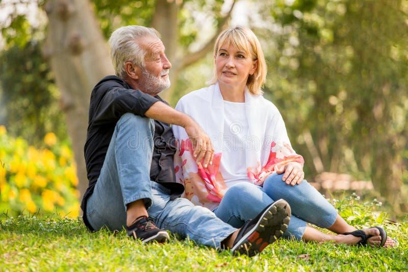 Het gelukkige hogere paar ontspannen bij park samen in ochtendtijd oude mensen die op gras in het de herfstpark zitten Het bejaar royalty-vrije stock fotografie