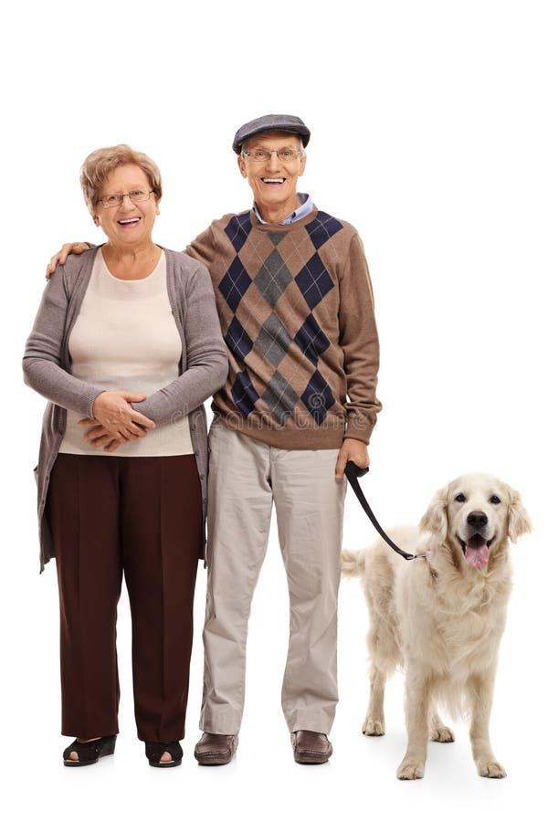Het gelukkige hogere paar stellen met hun hond stock afbeelding
