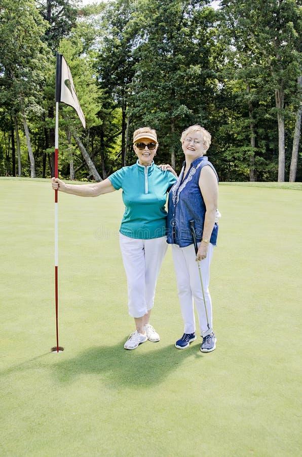 Het gelukkige hogere vrouwen golfing stock afbeeldingen