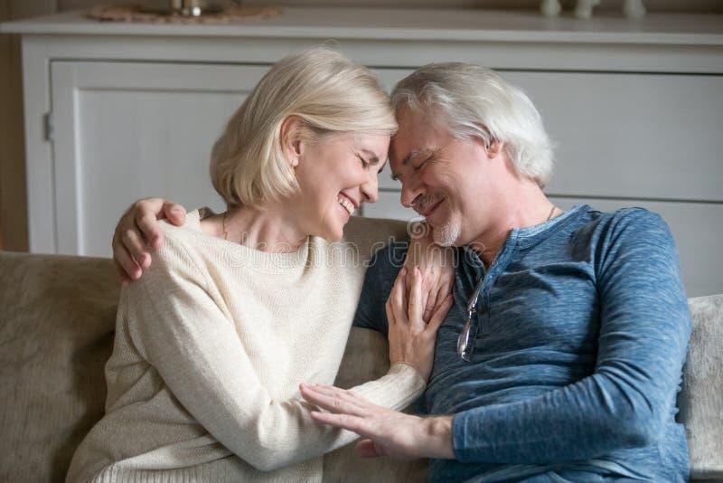 Het gelukkige het houden van rijpe romantische paar het lachen thuis omhelzen stock fotografie