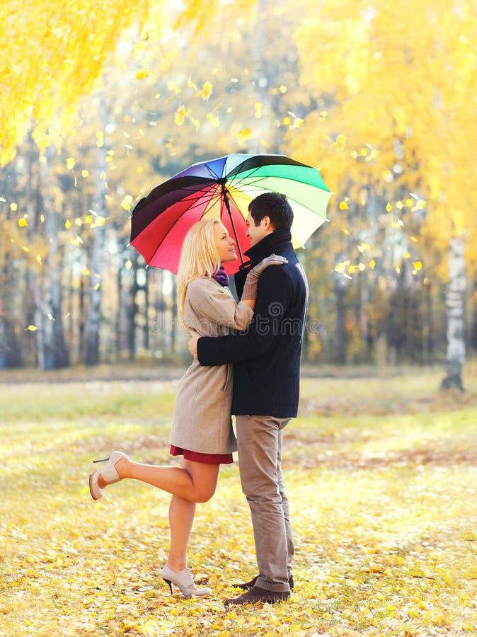 Het gelukkige houdende van paar die met kleurrijke paraplu samen in warme zonnige dag over het gele vliegen koesteren doorbladert royalty-vrije stock foto's